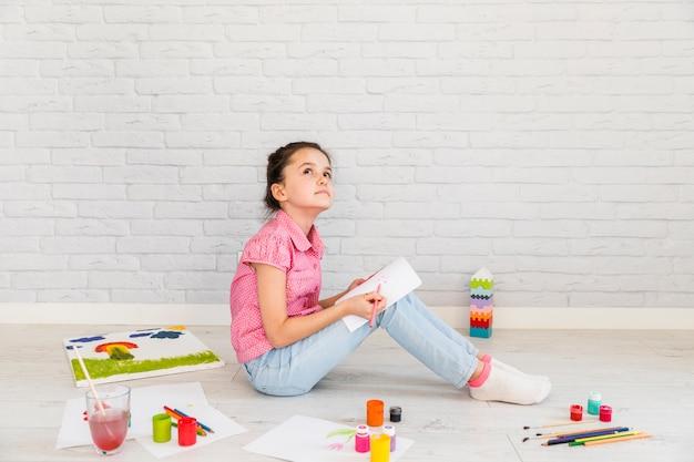 Erwogenes mädchen, das auf bodenzeichnung auf weißbuch mit farbigem bleistift sitzt