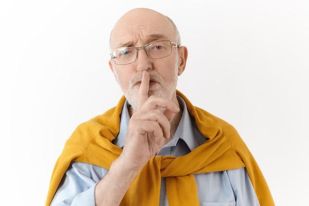 Erzähl es niemandem. menschliche mimik und körpersprache. ernsthafter älterer unrasierter glatzkopf in eleganter kleidung, der den vorderfinger vor dem mund hält, shh sagt und darum bittet, sein geheimnis zu bewahren