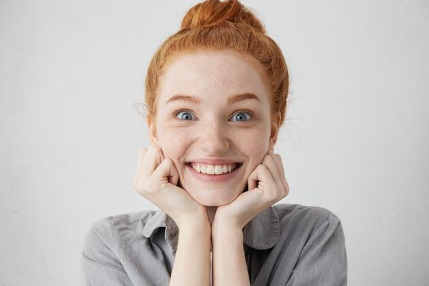 Erzähl mir mehr. nahaufnahme schuss der neugierigen 20-jährigen rothaarigen kaukasischen frau, die gesicht auf ihren händen kissen und mit vorfreude und aufregung schauen, während geschichte oder klatsch hören