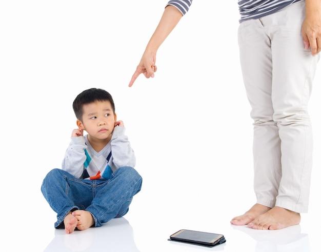 Erziehung des kindes. mutter schimpft mit ihrem kinderjungen auf smartphone.