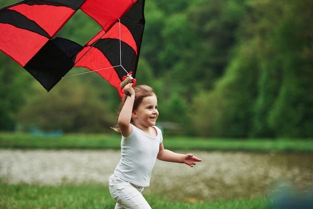 Es fühlt sich großartig an. positives weibliches kind, das mit rotem und schwarzem drachen in den händen draußen läuft