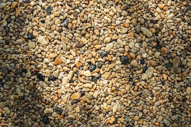 Es gibt glänzende nasse kieselsteine am strand der natürliche hintergrund und die textur des steins
