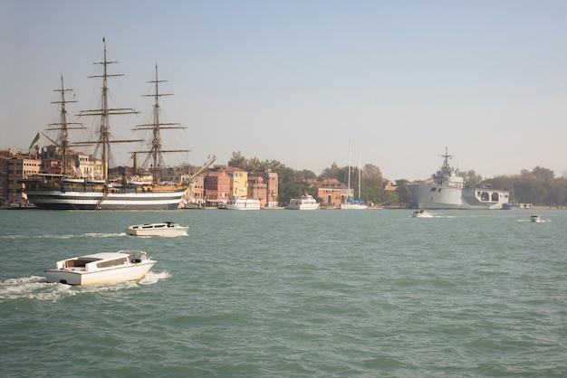 Es gibt schiffe in der nähe des piers, die größten sind ein altes segelschiff und ein neues flugzeug, das kreuzfahrten trägt