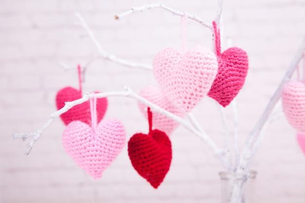 Es gibt viele rosa gestrickte herzen auf weißen zweigen. glasflasche. valentinstag.