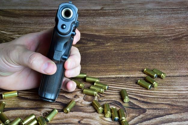 Es gibt viele verstreute patronen auf braunen holzbrettern sowie eine hand, die eine pistole mit einer in den rahmen gerichteten mündung hält.