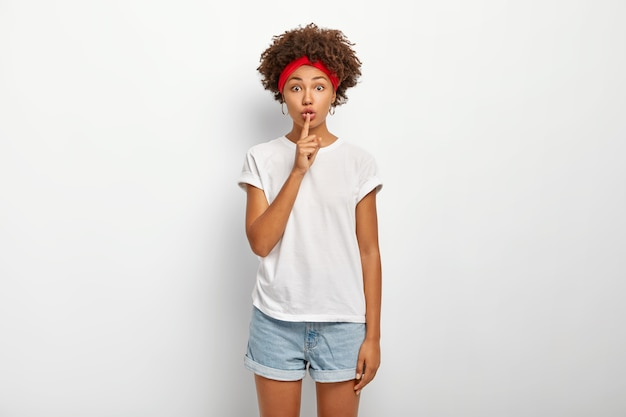 Es ist besser, ruhig zu bleiben. intensiv gestörte frau hat afro-frisur, erklärt tabu, macht schweigegeste, schweigeschild, trägt lässiges outfit, posiert gegen weiße wand. sprich nicht so laut