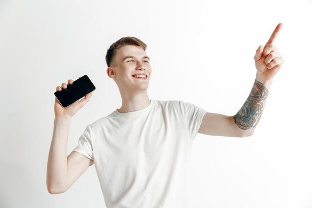 Es ist cool. gute nachrichten. mach das wie ich. junger gutaussehender mann, der smartphonebildschirm und unterzeichnungs-ok-zeichen lokalisiert auf grauem hintergrund zeigt. menschliche emotionen, gesichtsausdruck, werbekonzept.