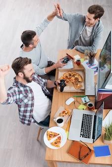Es ist das perfekte spiel! draufsicht auf drei glückliche junge männer, die computerspiele spielen, während sie am schreibtisch sitzen