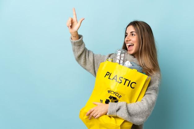 Es ist eine großartige idee, eine tüte voller plastikflaschen zu halten, um sie mit dem zeigefinger auf isoliertem blau zu recyceln