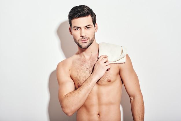 Es ist eine sehr schöne zeit für einen gutaussehenden mann, der ohne hemd steht und ein weißes handtuch hält