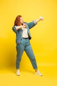 Es ist einfacher, anhänger zu sein. benötigen sie minimale kleidung für selfie. porträt der kaukasischen frau auf gelbem hintergrund. schönes weibliches rotes haarmodell. konzept der menschlichen emotionen, gesichtsausdruck, verkauf, anzeige.
