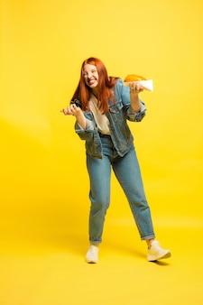 Es ist einfacher, anhänger zu sein. sie müssen nicht mit essen fotografieren. kaukasische frau auf gelbem hintergrund. schönes weibliches rotes haarmodell. konzept der menschlichen emotionen, gesichtsausdruck, verkauf, anzeige.