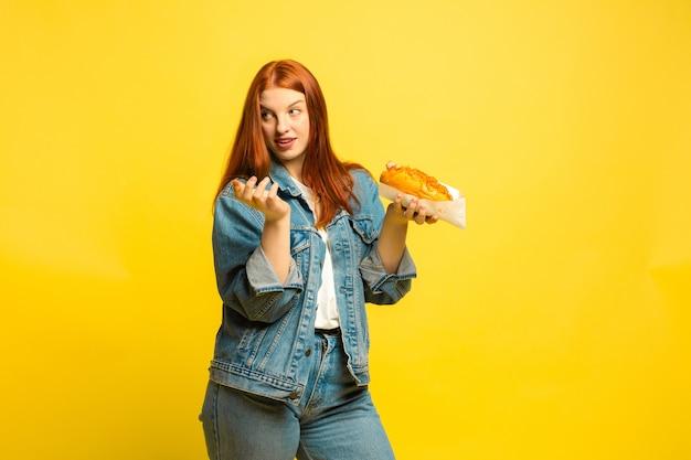 Es ist einfacher, anhänger zu sein. sie müssen nicht mit essen fotografieren. kaukasische frau ist auf gelbem hintergrund. schönes weibliches rotes haarmodell. konzept der menschlichen emotionen, gesichtsausdruck, verkauf, anzeige.