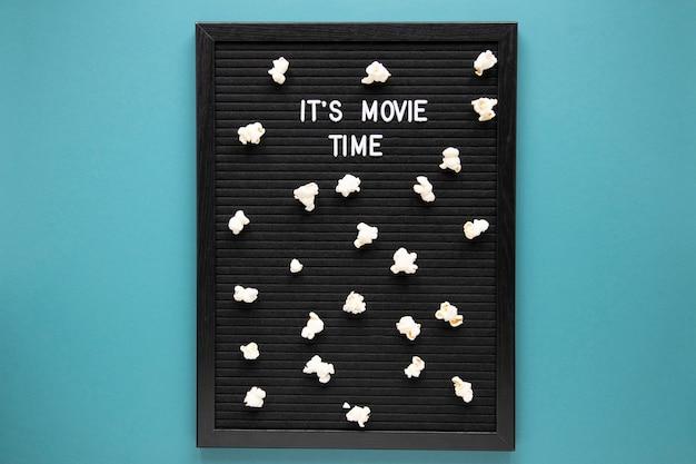 Es ist filmzeitbeschriftung auf schwarzem brett mit popcorn