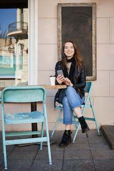 Es ist immer zeit für kaffee. porträt der glücklichen gutaussehenden frau, die in der terrasse des cafés sitzt, smartphone hält und schaut