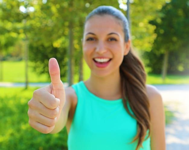 Es ist in ordnung! ich mag das! porträt des gewinnermädchens, das daumen oben zeigt. positive lächelnde fitness gesunde frau im freien. konzentriere dich auf die hand.