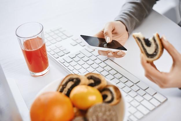 Es ist keine zeit zum entspannen. hauptmitglied der firma wurde krank und arbeitete von zu hause aus, kann nicht für die pause ablenken, so dass sie zu mittag isst, während sie informationen im smartphone sucht und mit dem computer arbeitet