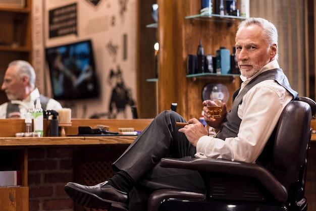 Es ist mein geschäft. hübscher bärtiger älterer mann, der auf ledersessel mit whiskyglas und zigarre vor spiegel am friseursalon sitzt.