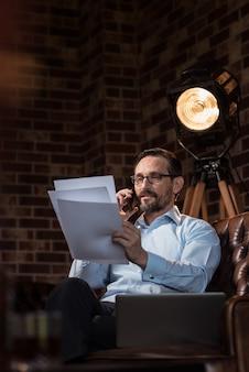 Es ist mein job. attraktiver erfolgreicher stilvoller geschäftsmann, der einige blätter papier hält und sie beim telefonieren betrachtet
