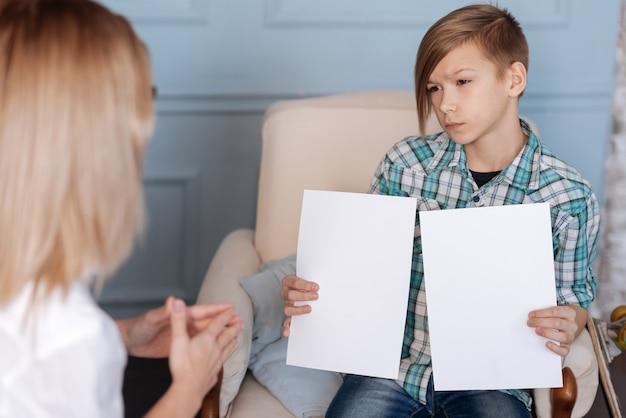 Es ist nicht interessant. hübscher ernsthafter teenager, der freizeitkleidung trägt, die zwei weiße papierblätter hält, während er seine lippen drückt