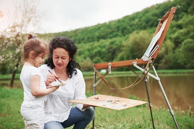 Es ist nicht so schwer. enkelin das malen beibringen. in der natürlichen parklandschaft