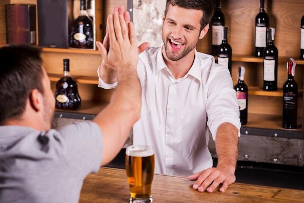 Es ist schön, dich wiederzusehen! rückansicht eines männlichen kunden, der mit dem barkeeper spricht, während er an der bartheke sitzt