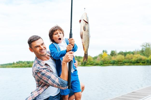 Es ist so groß! vater und sohn strecken eine angelrute mit fisch am haken, während der kleine junge aufgeregt aussieht und den mund offen hält