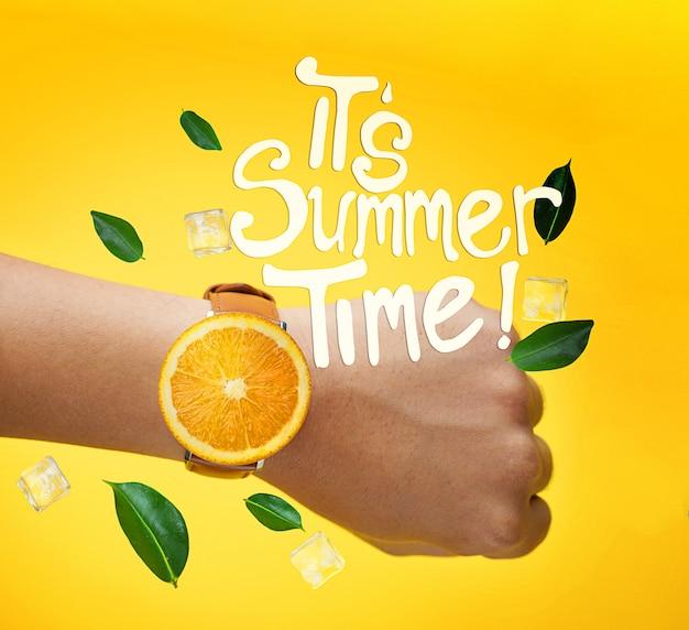 Es ist sommerzeit typografie. männliche hand, die frucht-orange uhr-grün-blätter und eis-junges trägt