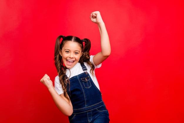 Es ist weihnachtszeit! foto der schönen kleinen dame positive stimmung neujahrsfeiertage, die fäuste heben letzten lerntag tragen lässige jeans insgesamt weißes t-shirt isoliert roten farbhintergrund