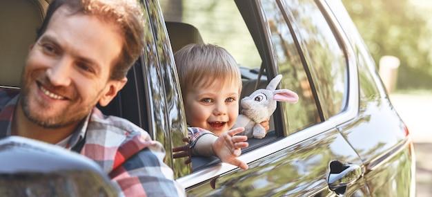 Es ist zeit für ein weiteres abenteuer, süßer kleiner kaukasischer junge, der im auto sitzt und sucht