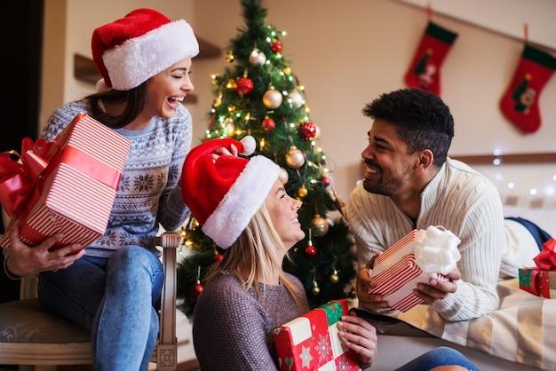 Es ist zeit für geschenke! gruppe von drei glücklichen freunden, die neujahrsgeschenke teilen. sitzen in einem raum mit schöner neujahrsdekoration.