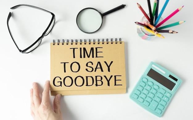 Es ist zeit, goobye-text zu sagen, der auf einem notizbuch, einem taschenrechner, bleistiften, einer lupe auf einem tisch geschrieben ist