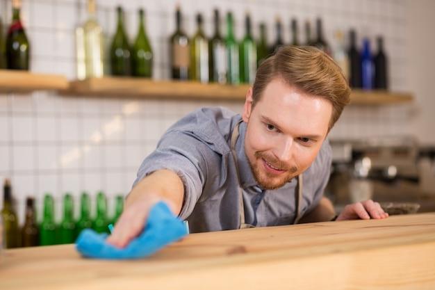 Es muss sauber sein. angenehmer netter positiver mann, der einen staubtuch hält und den tisch während der arbeit putzt