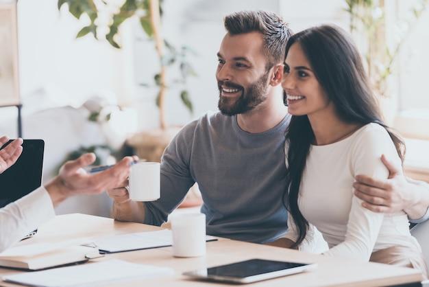 Es scheint ein guter vorschlag zu sein. fröhliches junges paar, das sich miteinander verbindet und lächelt, während es einen mann ansieht, der vor ihnen sitzt und gestikuliert