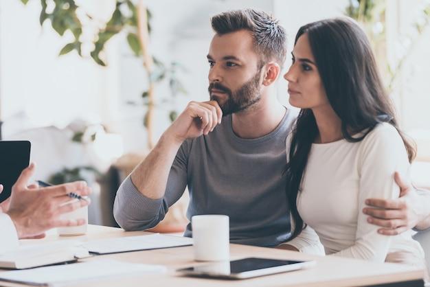 Es scheint ein guter vorschlag zu sein. konzentriertes junges paar, das sich miteinander verbindet und einem mann zuhört, der vor ihnen sitzt