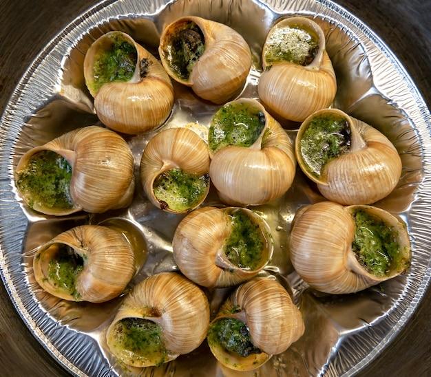 Escargots de bourgogne-schnecken gefüllt mit kräutern und öl.