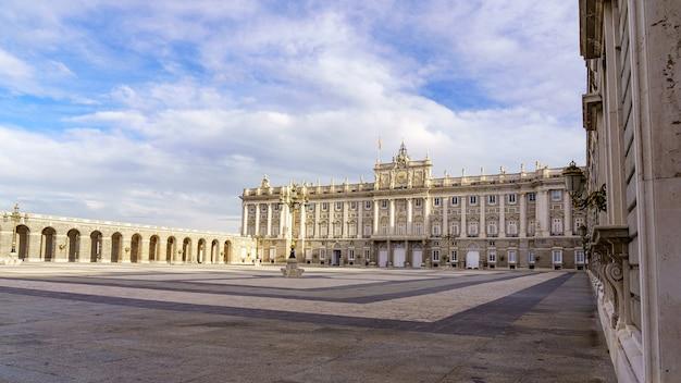 Esplanade und großer innenhof des königlichen palastes von madrid bei sonnenaufgang an einem tag mit blauem himmel und wolken. spanien.