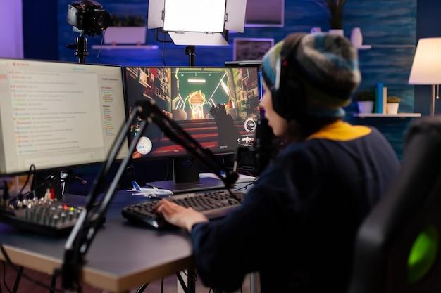 Esport-streamer, der ein shooter-spiel mit anderen spielern im streaming-chat für einen virtuellen spielewettbewerb spielt. spieler, die online-videospiele mit neuen grafiken auf einem leistungsstarken computer erstellen