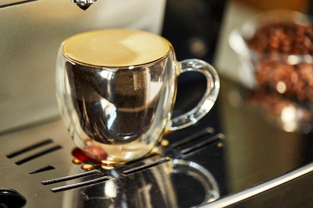 Espresso in einer transparenten tasse, stehend auf einer kaffeemaschine mit reflexion. frisch gebrühter kaffeekonzept