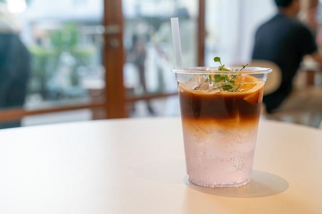 Espresso-kaffee-tonic mit yuzu-orange im café-restaurant