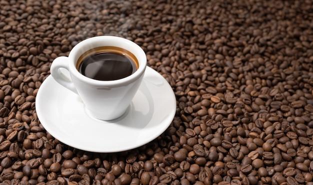 Espresso kaffeetasse auf gerösteten bohnen hintergrund. platz kopieren