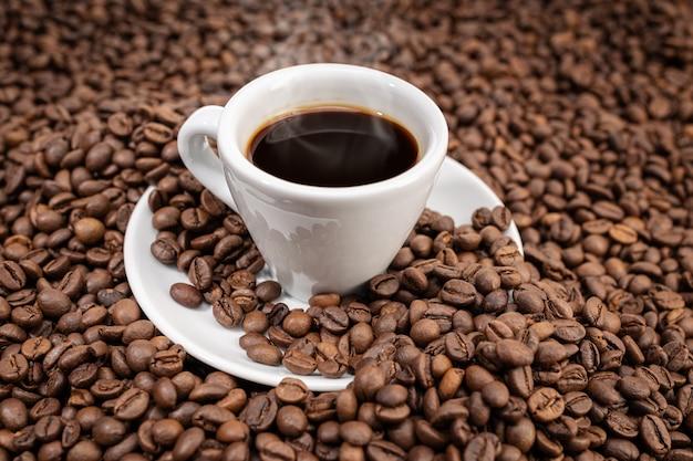 Espresso kaffeetasse auf gerösteten bohnen hintergrund