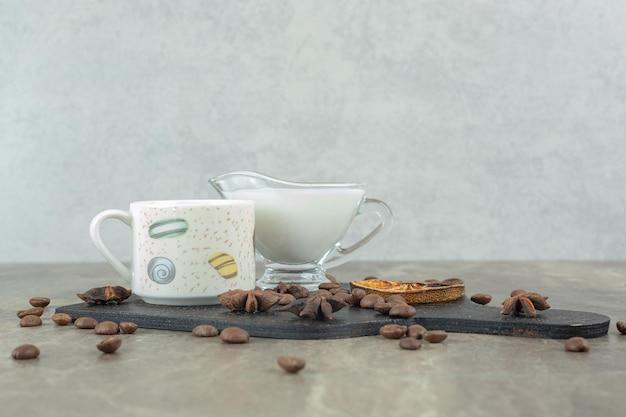 Espresso, milch und kaffeebohnen auf dunklem brett