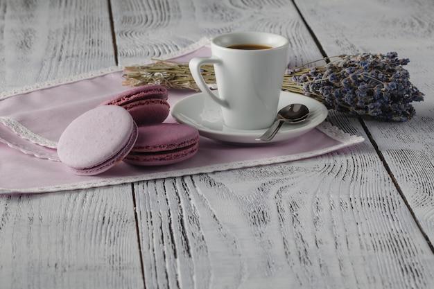 Espresso mit französischen makronen auf schäbigem schickem hintergrund