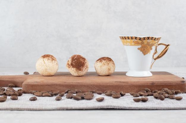 Espresso und kekse auf holzbrett mit kaffeebohnen