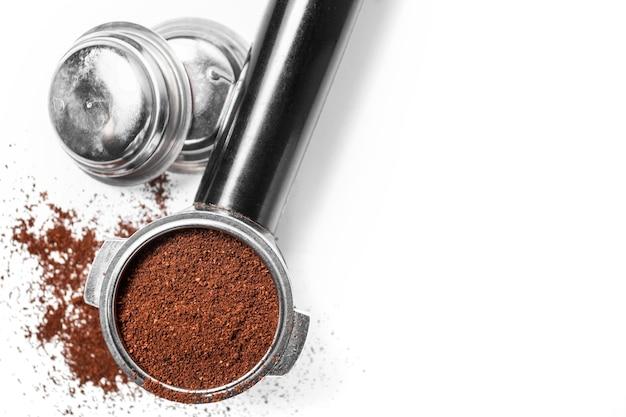Espressohalter und austauschbare kaffeefilter. das horn aus der kaffeemaschine auf einem weißen