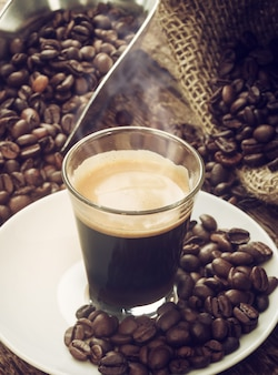 Espressokaffee in der glasschale mit kaffeebohnen.
