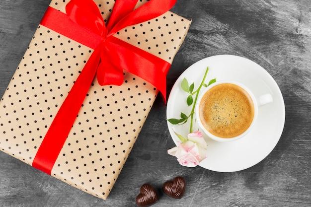 Espressokaffee in einer weißen schale, in einer rosa rose, in einem geschenk mit einer bürokratie und in schokoladen auf einem dunklen hintergrund. ansicht von oben. essen hintergrund