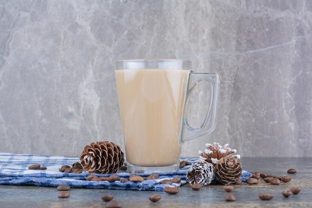 Espressokaffee mit tannenzapfen und kaffeebohnen auf tischdecke. foto in hoher qualität