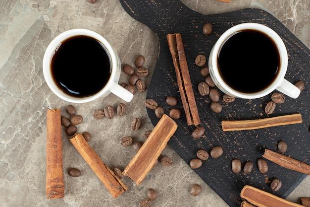 Espressokaffee, zimtstangen und kaffeebohnen auf marmoroberfläche